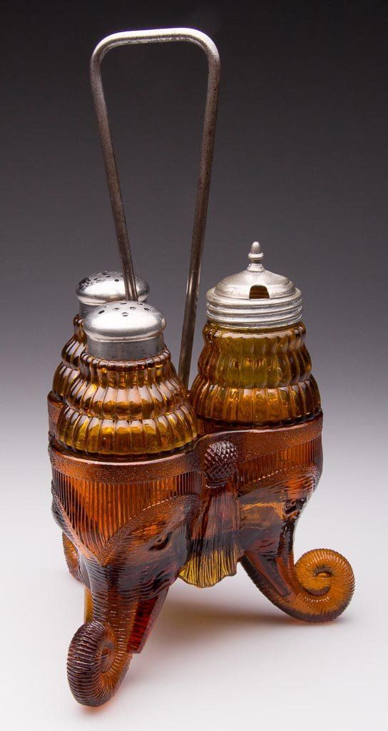 """JUMBO / STANLEY THREE-BOTTLE CASTER SET, amber, comprising two shakers and a mustard in original glass stand with center handle, period lids. Greensburg Glass Co. Introduced in 1891. 3"""" to 9 1/2"""" HOA."""