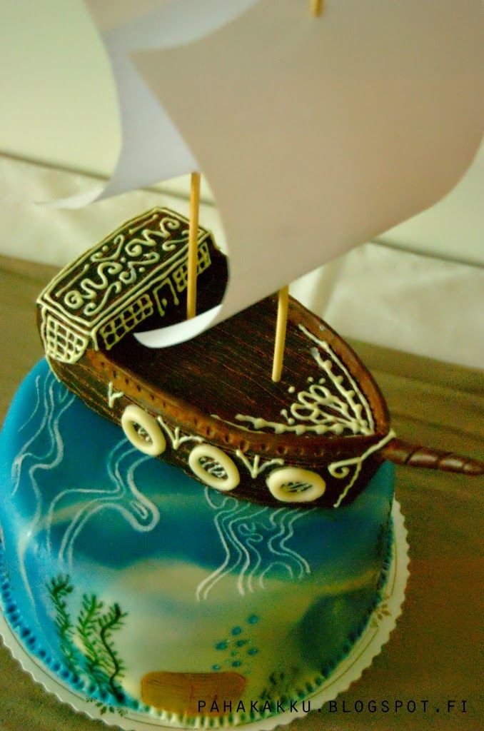 A pirate ship cake. The cake is covered with marbled marzipan and painted with edible colors. the ship is made of home-made rice krispie treats and covered with modeling chocolate.
