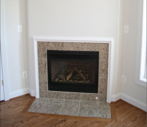 Fireplace with simple builder grade moulding around tile ...