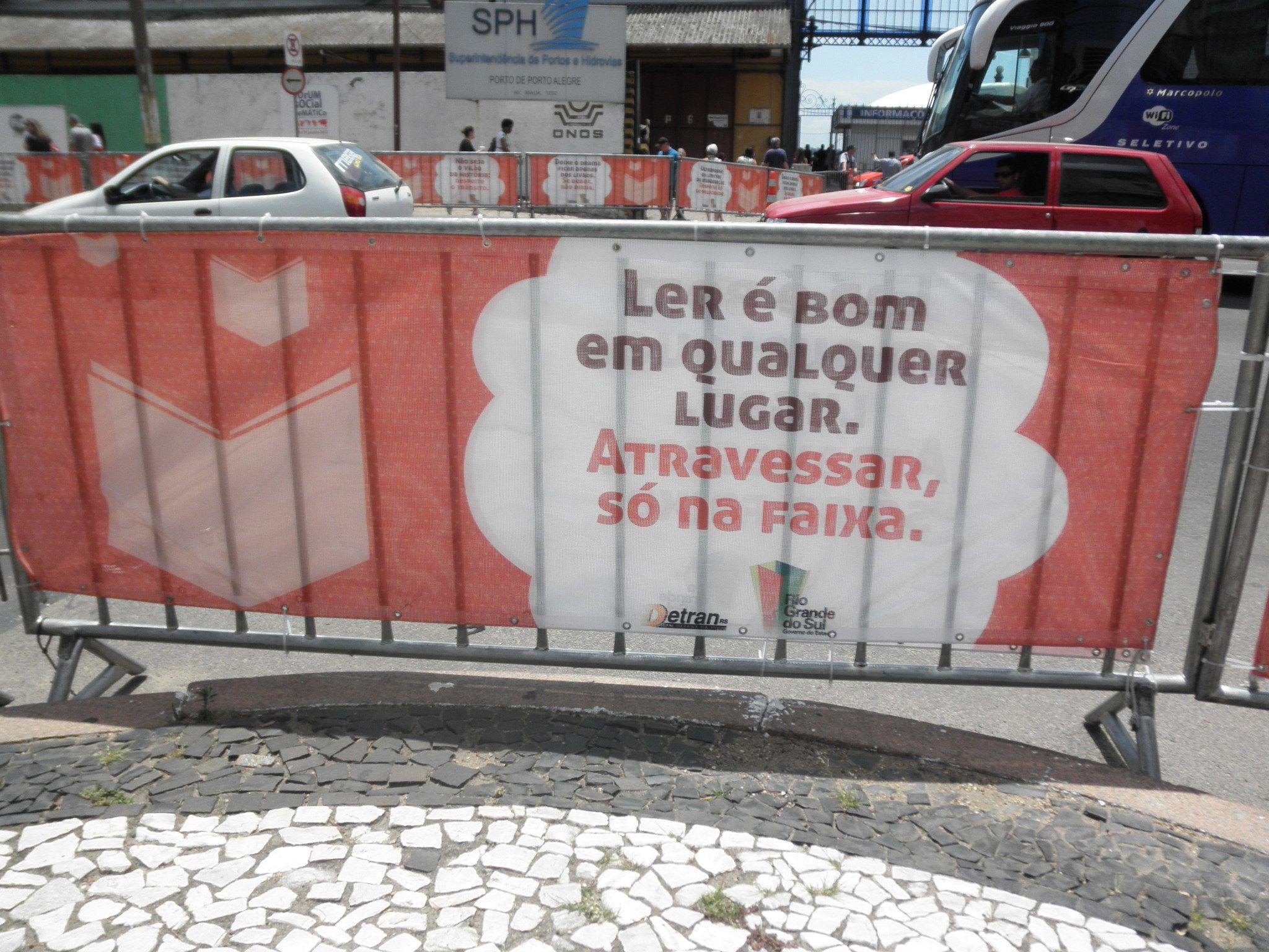"""Separadores para paso peatonal Feria del Libro de Porto Alegre 2012: """"Leer es posible en cualquier lugar, cruzar la calle sólo en la cebra""""."""