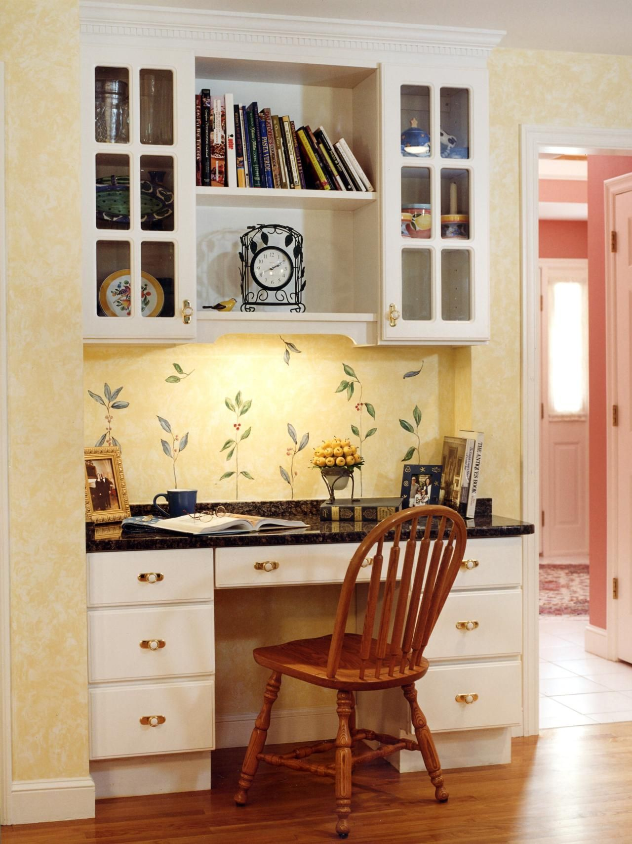 This sunny cottage-style kitchen features a built-in desk and ...
