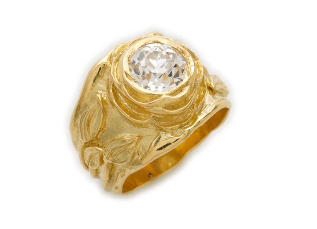 A molten gold rose ring. Set in the flower's centre is an elegant old cut diamond. The sides are decorated with leaves and a molten edge.   Luxify   Luxury Within Reach