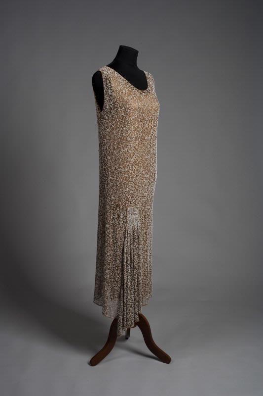 MMI 001651 :: klänning Klänning av maskinvävd bronsfärgad tyll med vita och enstaka blå pärlor. Passpoaler av bronsfärgat siden runt hals, ärmringning, midja och nederkant. Rak modell, avskuren på höften och med nederdelen omlott från ett hopdraget parti. Nederkanten osymmetrisk.