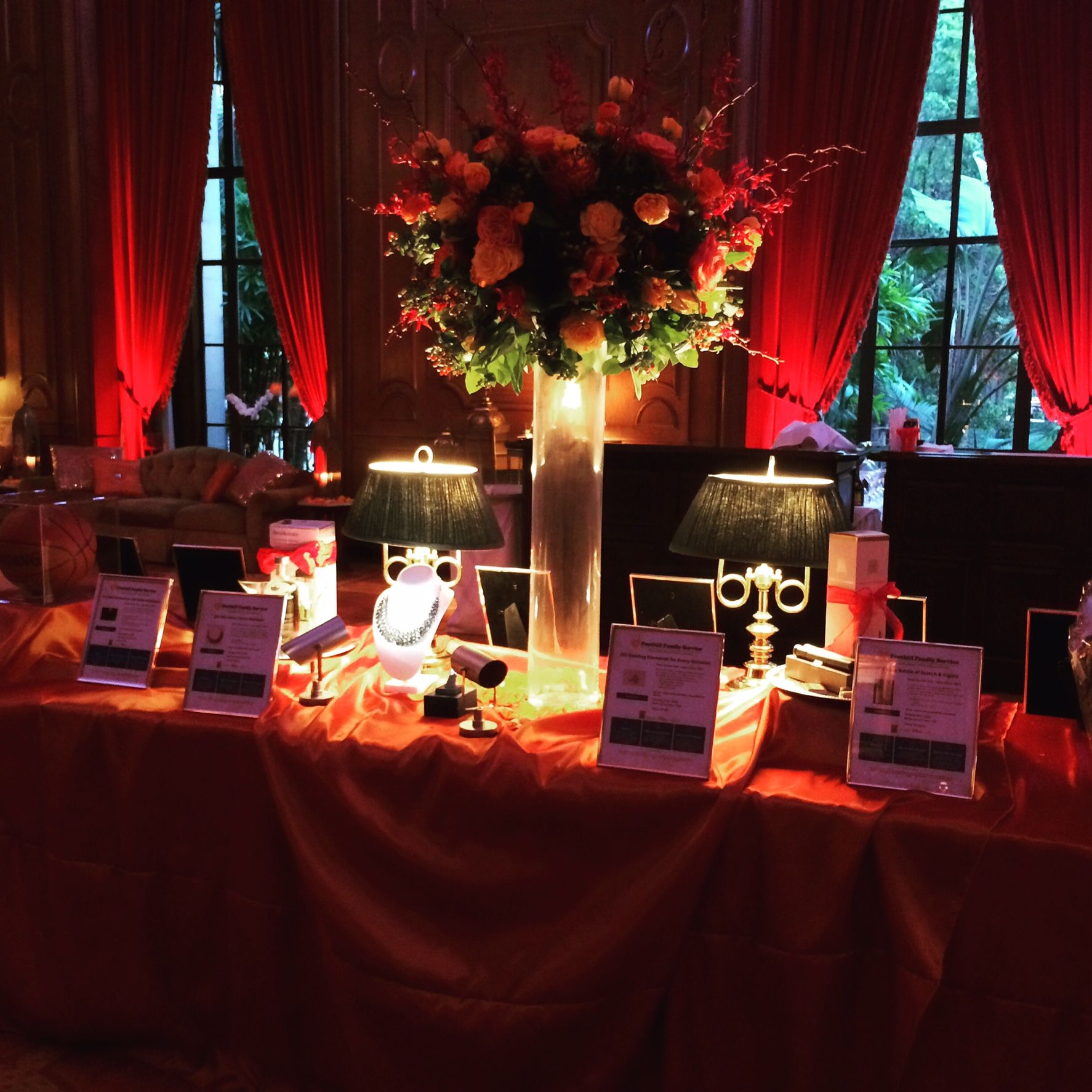 red dramatic classy silent auction table with roses and uplights silent auction