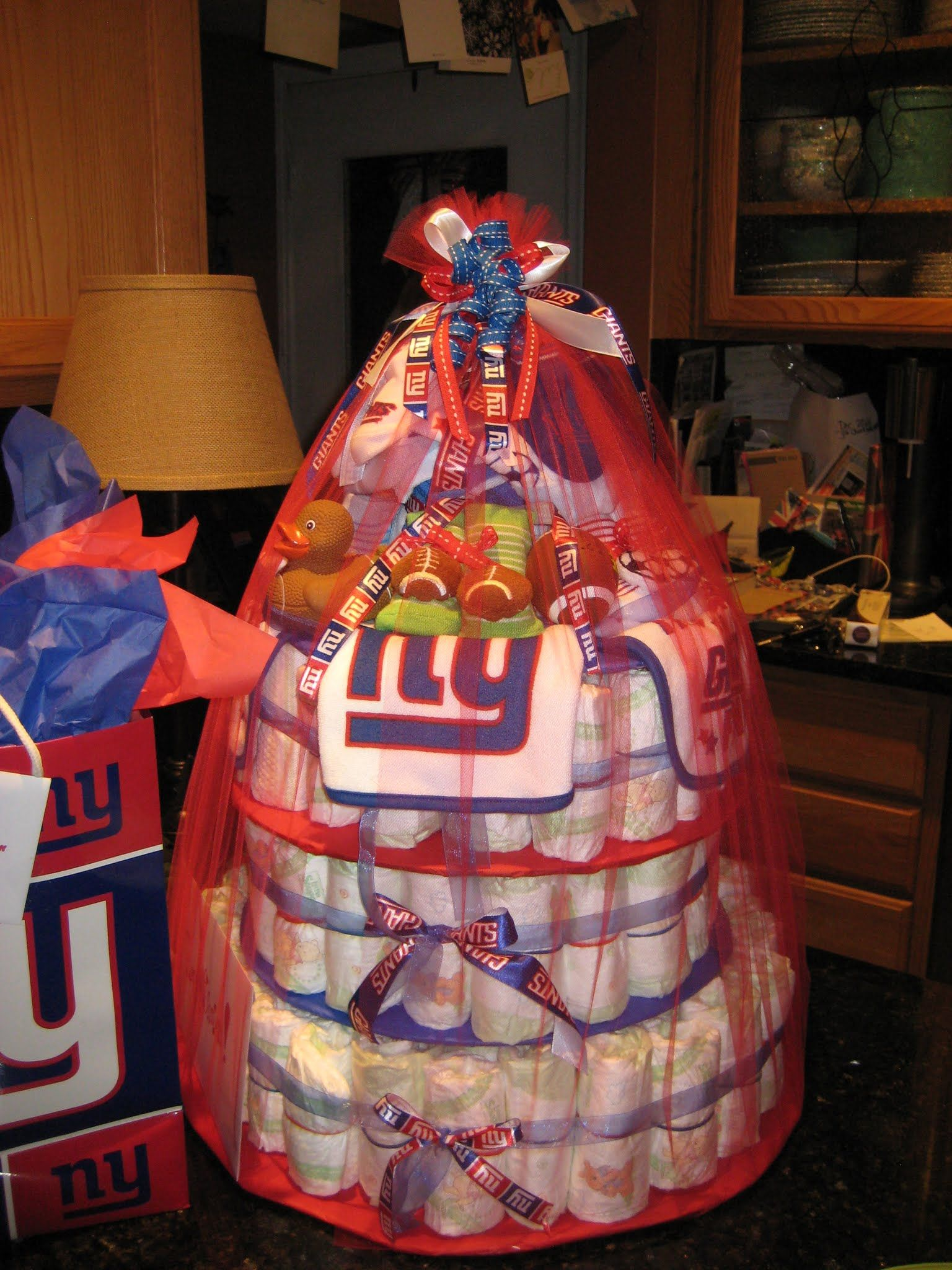 NFL Giants themed baby diaper cake for baby shower gift. Made of three tiers of Huggies sizes  1 and 2  totaling 120 diapers rolled w/ red and blue rubber bands.