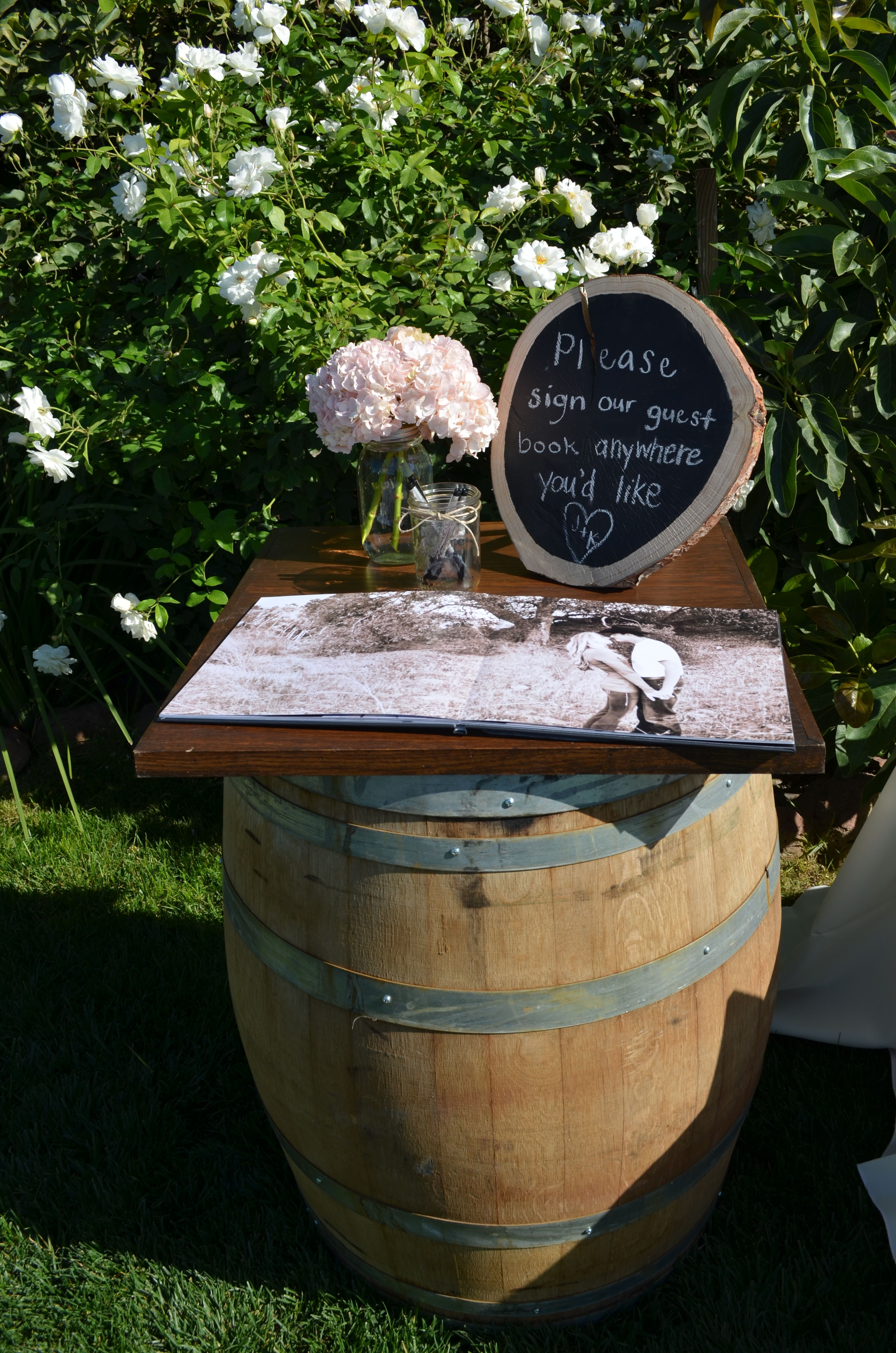 Wine barrel with wood top as a guest book table Wine