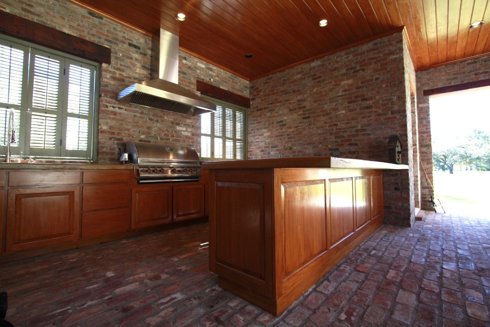 Custom Cypress outdoor kitchen with raised panel and slab ...
