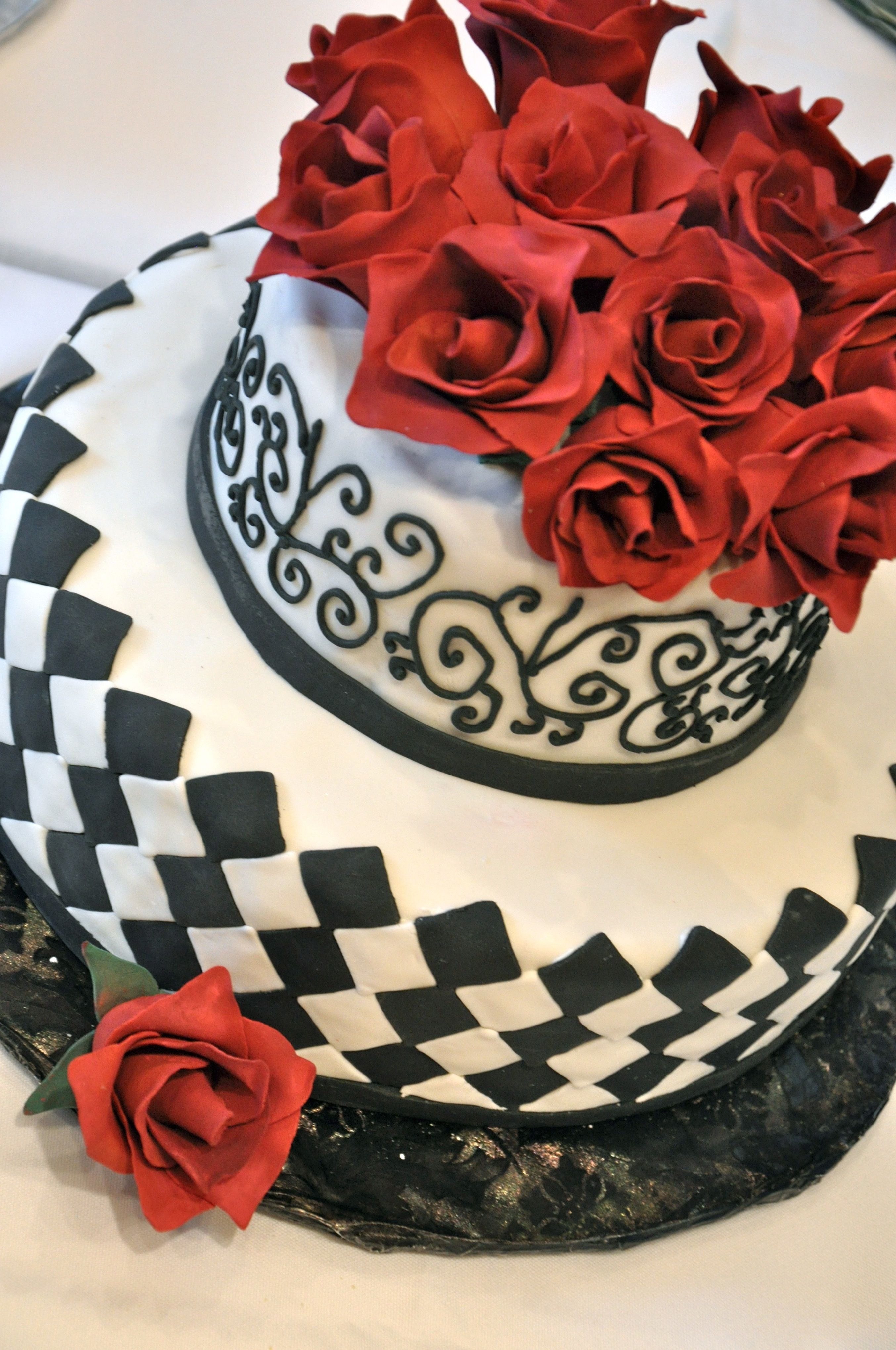 A Black And White Cake With Red Gumpaste Flowers Made By An Ice