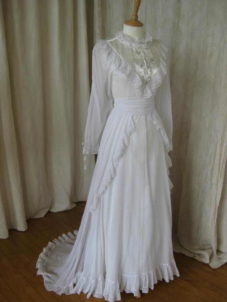 A beautiful vintage wedding dress with a train of fine  and floaty cotton from ex Liberty of London designer Bernard Foong. The dress is very original with a hand painted yoke with applied sequins,and lace edged ruffles surrounding the bodice. There is a pretty double lace trim to the neck, cuffs, sash, skirt hem and overskirt. The skirt of the dress is fully lined and has an intergral layer of net.