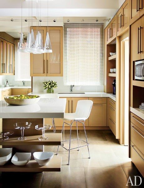 A ceiling fixture by Flos overlooks the kitchen, which is lined with rift-cut-oak cabinetry   archdigest.com