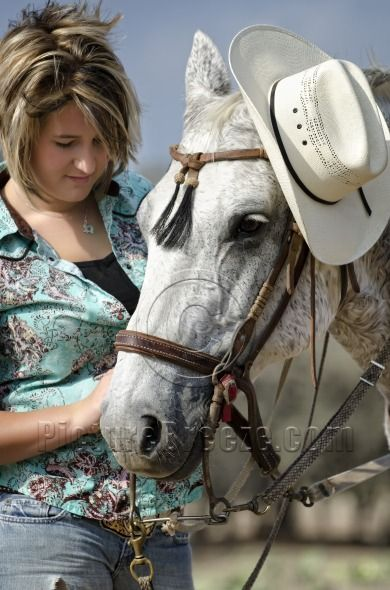 Cowgirl with her horse wearing hat | Stock Photo