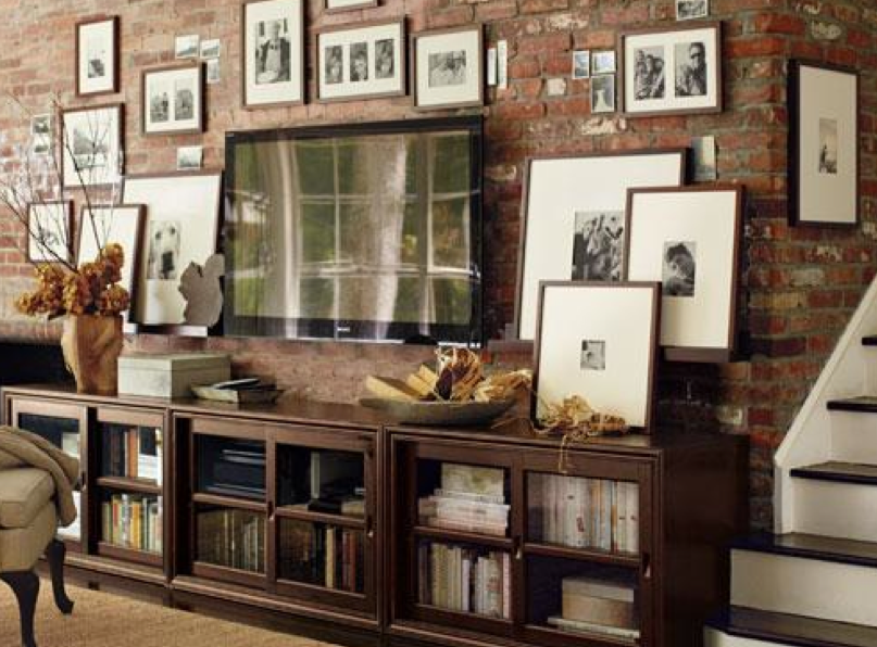 TV console surrounded by black & white portraits (PB