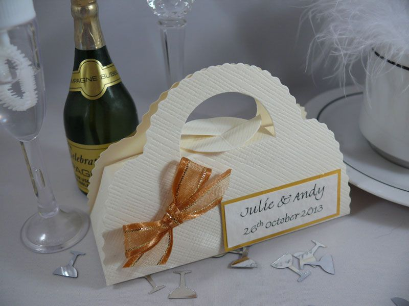 Ivory silk handbag favour box, decorated with gold ribbon and personalised with label