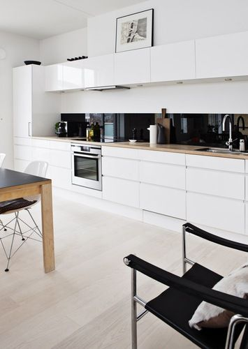 All white gloss kitchen with wooden countertops and black glass splash back.