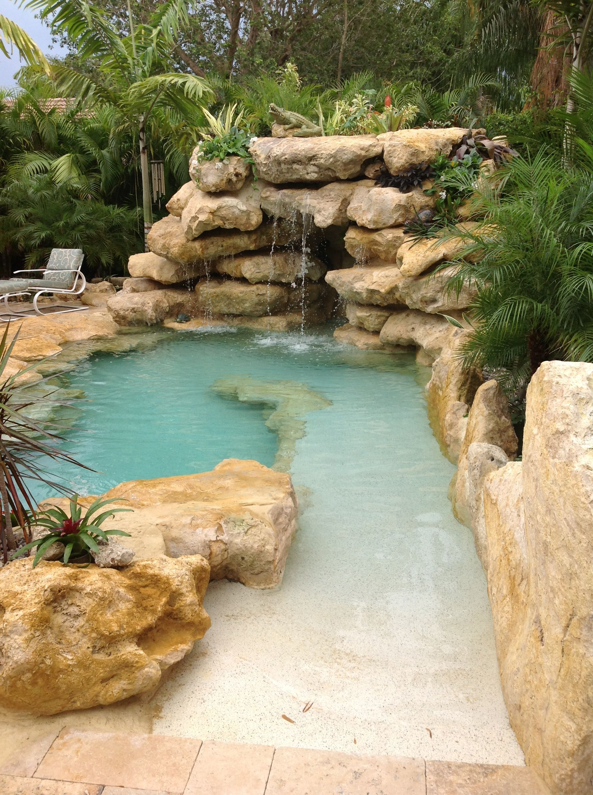 Sand entrance to our latest all natural stone tropical style pool.