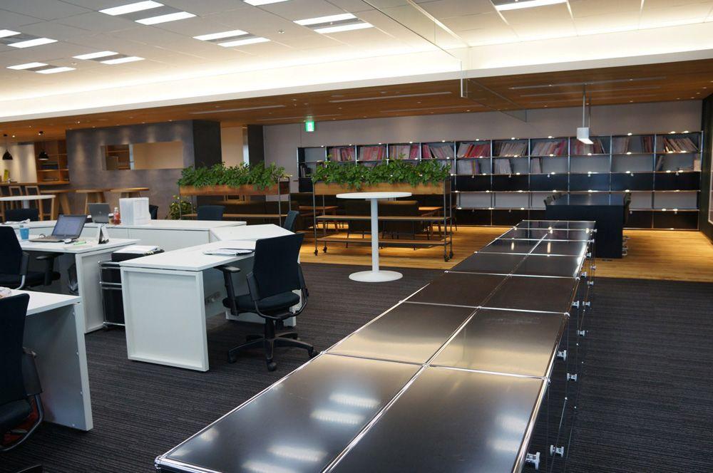 執務スペースの収納棚まわり。奥に見える木の空間は、後述するコミュニケーションライブラリー(写真:守山 久子)扇形レイアウトや席替えで活性化、クロスカンパニー|日経BP社 ケンプラッツ
