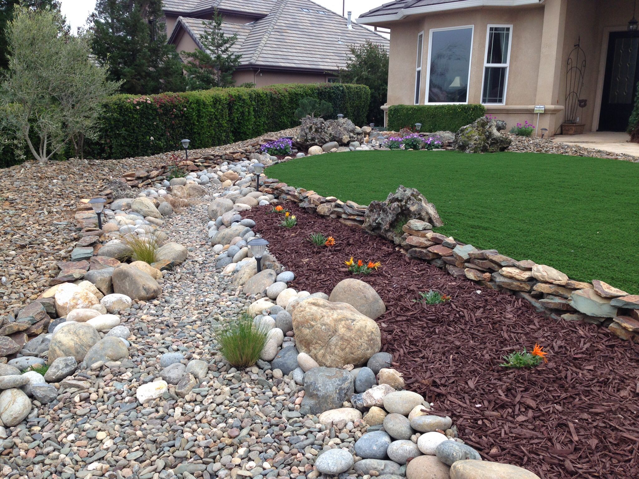 Drought tolerant landscape. Dry creek bed, artificial turf