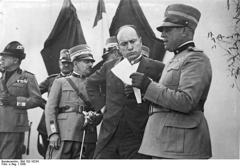 """Mussolini (in civilian garb) during inspection of a military airfield in 1930. Like Hitler, Mussolini accelerated the modernization of the Italian armed forces as part of his grand plan to create a """"new Roman empire"""". The grand plan ended in disaster in 1943-44."""