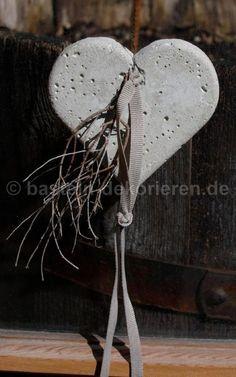 Photo of Hjerte laget av betong dekorert med et satengbånd og en liten gren.