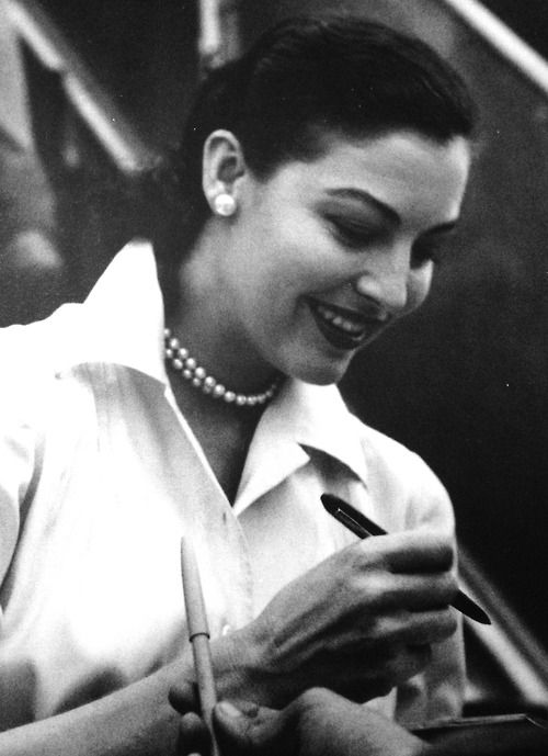 Ava Gardner signing autographs at a Singapore airport, 1954.