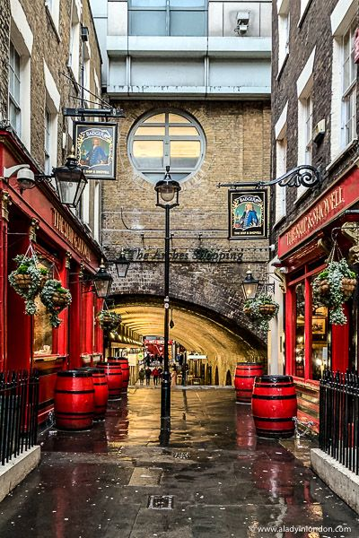 A historic alley with red pubs and barrels in London, England. Click through for more pictures on the A Lady in London blog.   #london #pub #england #alley
