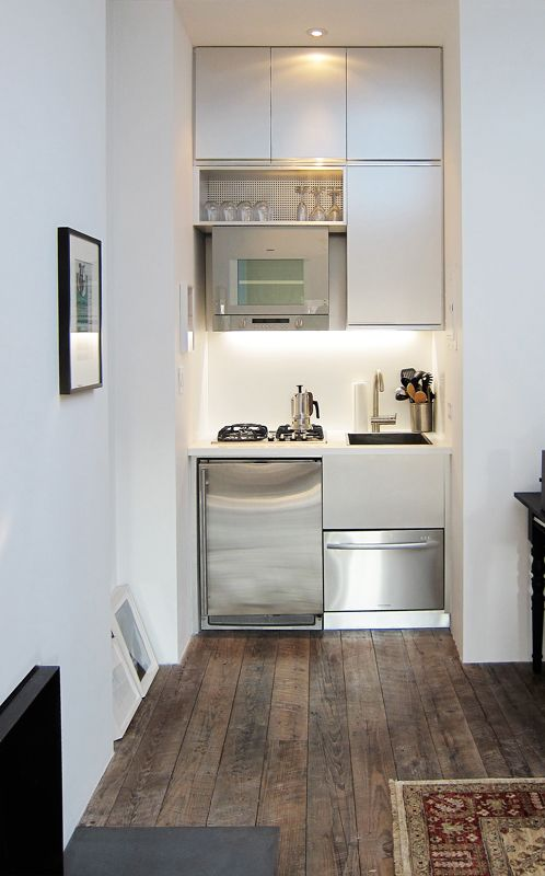 A tiny kitchen by Mesh Architectures occupies a nook in a 300-square-foot art dealer's sky-lit top-floor studio in a West Village low-rise. The high-mounted oven includes a space-saving feature where the bottom drops down for you to insert the food then retracts back up into the heat.