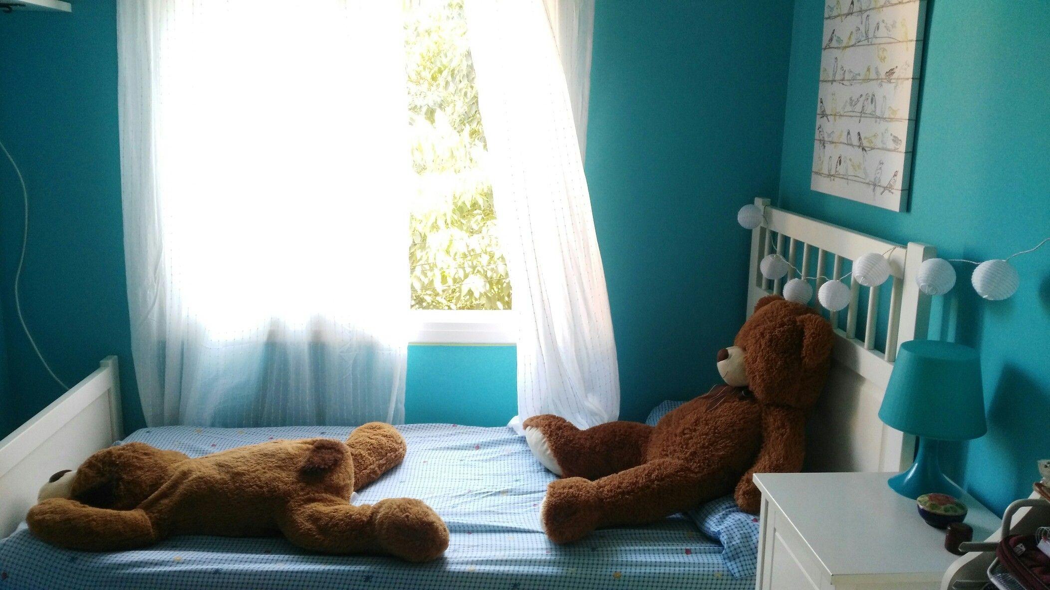 Peluches de decoración encima de la cama.