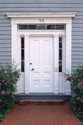 A White Door With Transom And Sidelights Is Centered In A