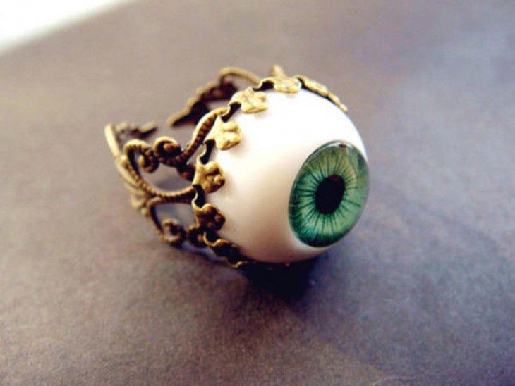 fotografía de anillo con un globo ocular en color blanco y verde y lineas doradas sobre una superficie de color café