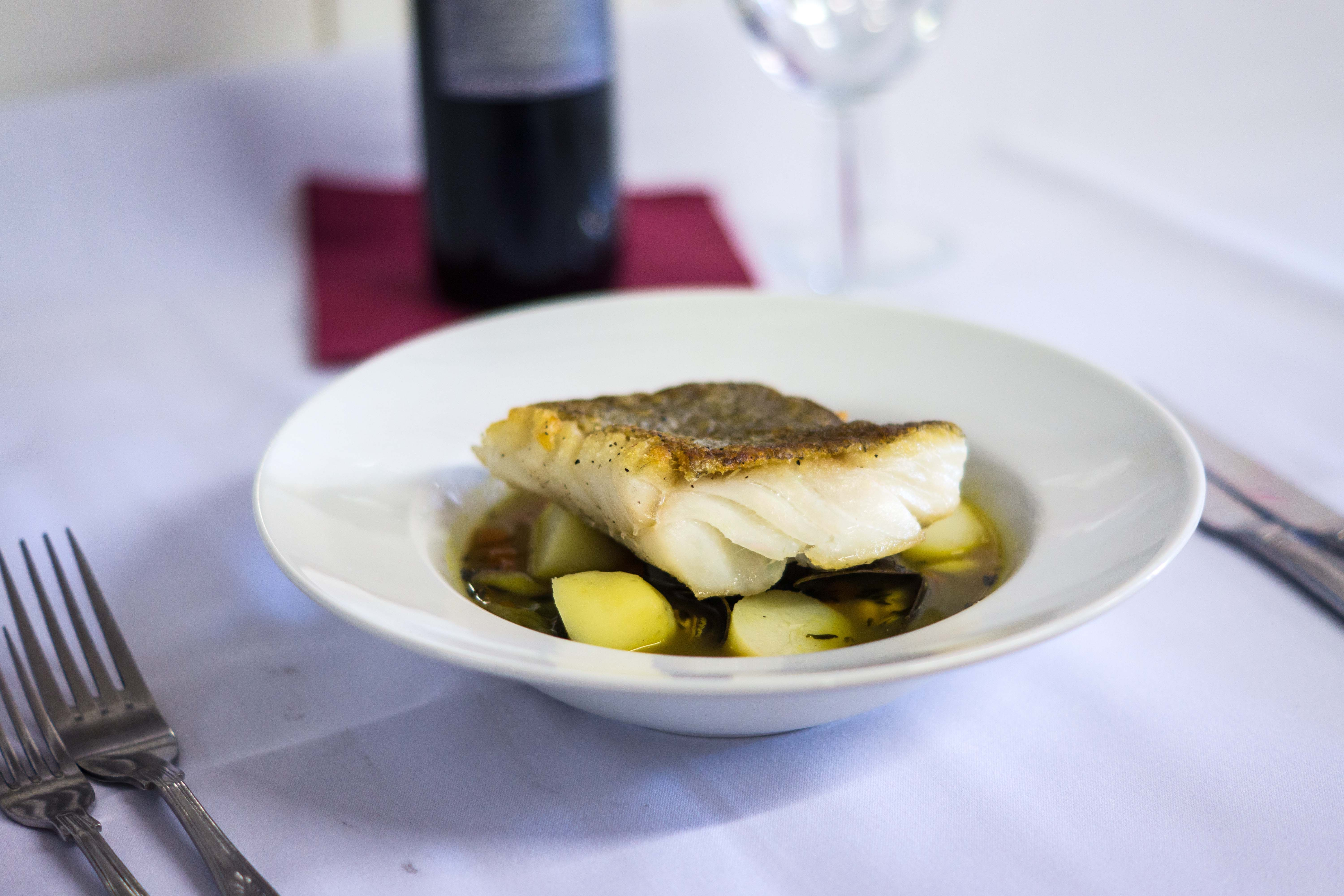 Pan fried fillet of sea bass with saffron fondant potato, wilted spinach, green beans, chilli and ginger cream reduction