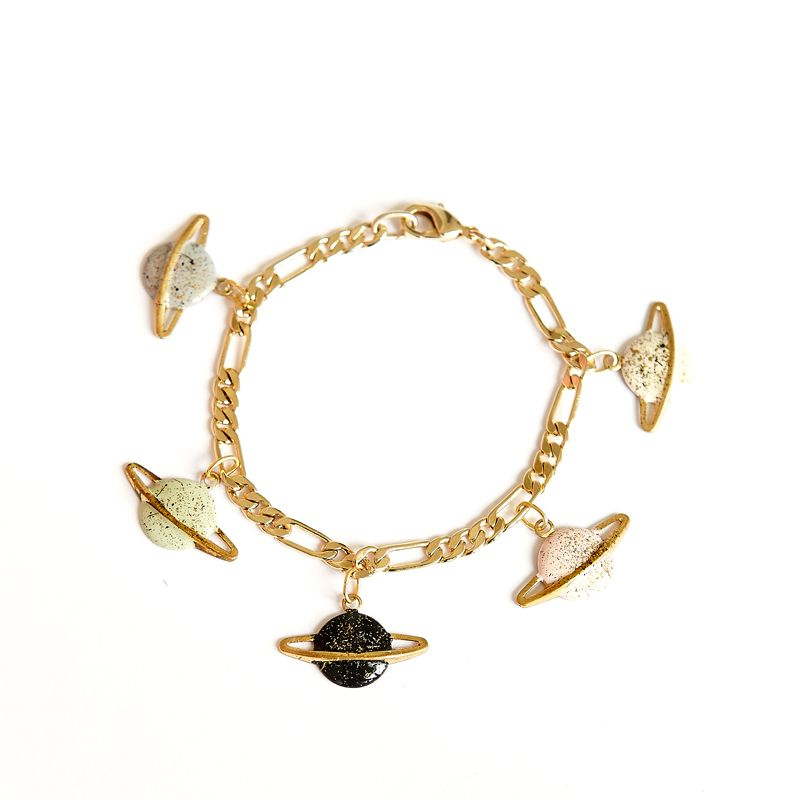 Saturn bracelet is one of Après ski's classic accessories inspired by the cosmos.A dreamy bracelet with five little Saturn charms hanging from a thick golden brass chain. Each charm is glazed by hand in a palette of pastel colours and sprinkled with gold.Bracelet length: 16 cm. Saturn charm: 2 cm. (W) x 1,3 cm. (L)<i>La pulsera Saturno es uno de los modelos clásicos de Après ski inspirados en el cosmos.Una pulsera encantadora con cinco miniaturas en lat�...