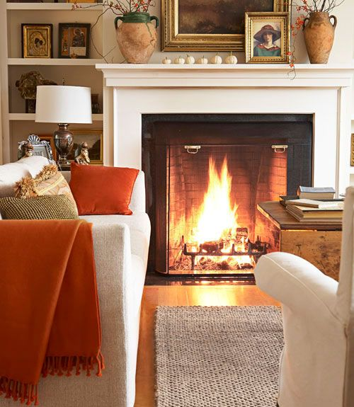 The living room of New Hampshire home with a fireplace, with burnt orange and gold-detailed throw pillows. A nubby cream sofa and white-slipcovered chair are from Crate and Barrel.     - CountryLiving.com