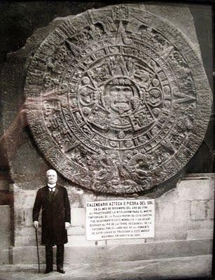 Porfirio Díaz standing next to the Aztec Sun Stone.