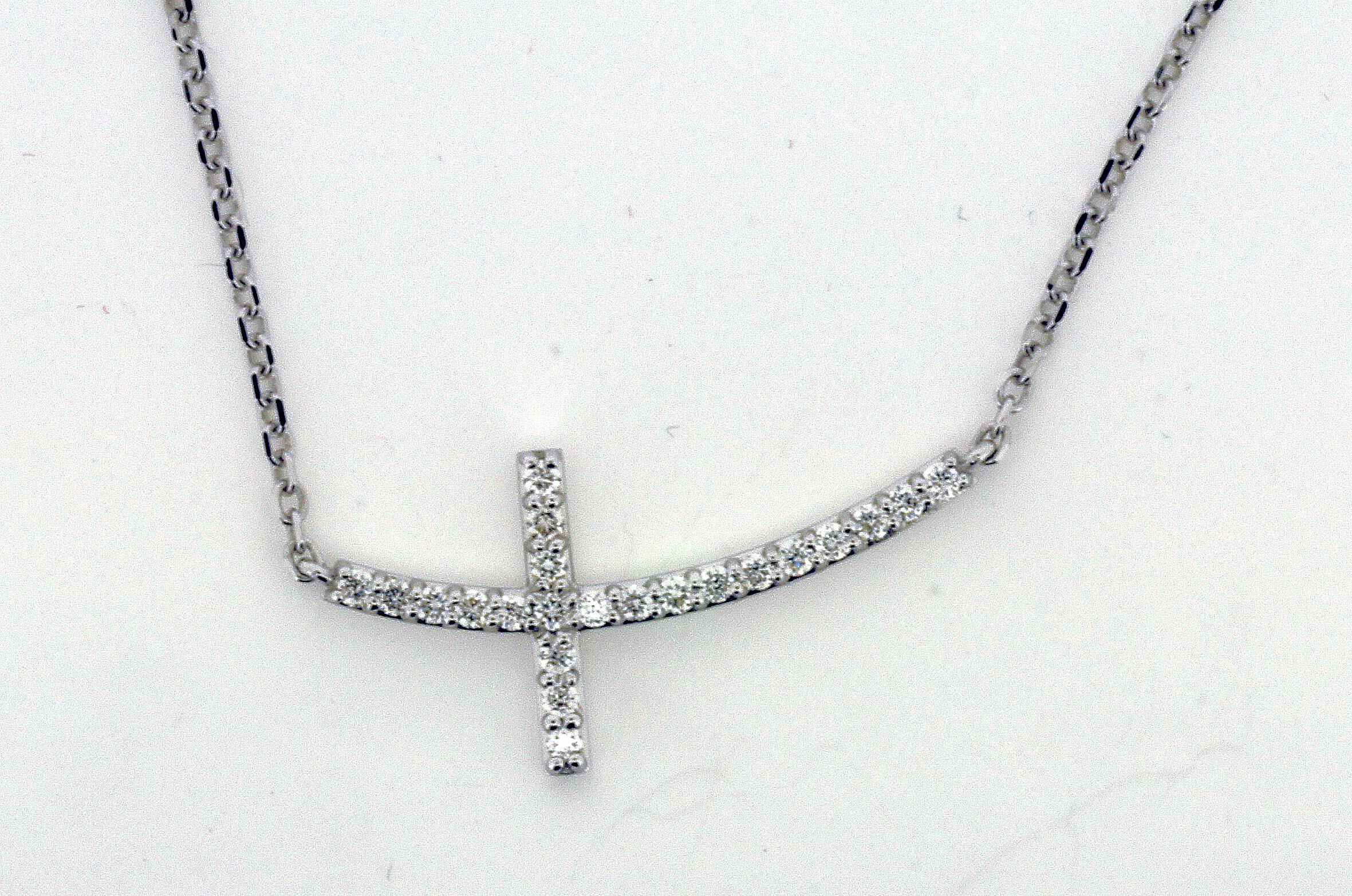 14 karat white gold with twenty two round brilliant cut diamonds prong set. The diamonds are G-Color and VS2 Clarity.The cross is suspended on a diamond cut cable chain that is 1.5 mm thick with a lobster clasp. The piece is a total of 18inches long but can be shortened to any length,the cross itself is 28 x 14mm. This item weighs approximately 4grams.
