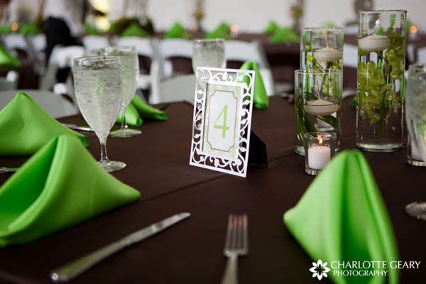 brown table cloth, green plant center pieces, green napkins, and ...
