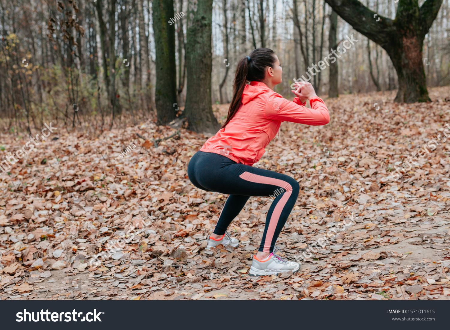 Young woman do squats outdoor on autumn leaves at the park. ,