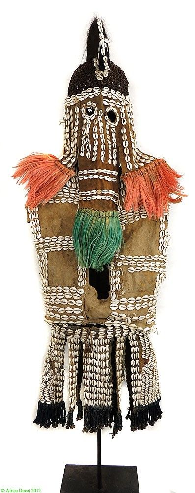 Africa | Maiden mask costume from the Dogon people of Mali | Cotton cloth, cowrie shells and plant fiber | Mid 20th century | Complete costume including an helmet mask in the form of a cowl surmounted by a high longitudinal crest coiffure, a tunic without sleeves, and a skirt made of several layers. This coiffure recalls the ceremonial hairstyle worn by the Peul, Fulbe, and Fulani women.