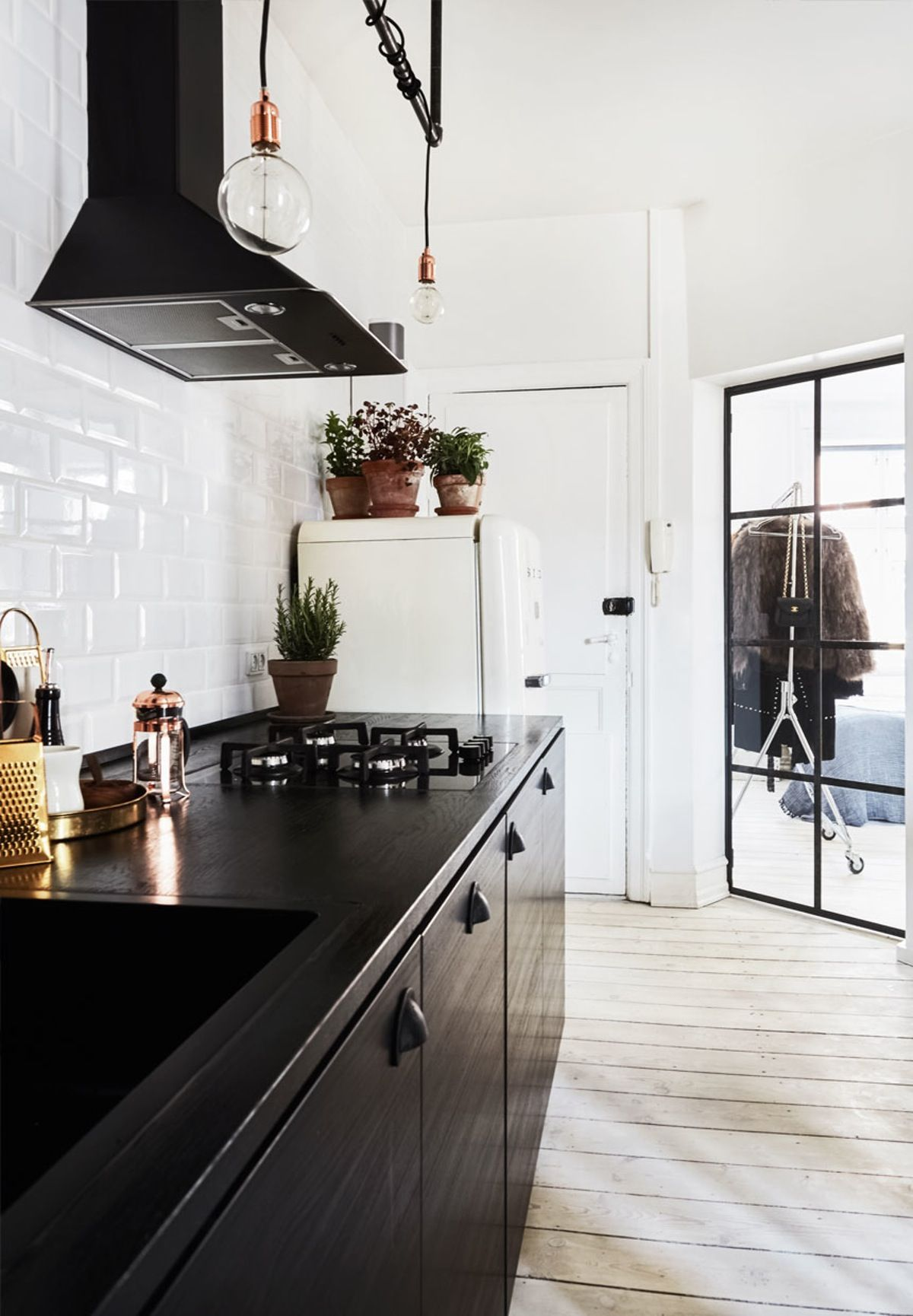rustic and cool kitchen with black wooden cabinets and tabletop and white subway tiles on the wall - Subway Tile House Interior