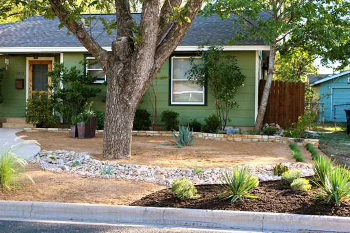 the grade change and soft curves of the dry creek bed give this front yard a soft  warm look