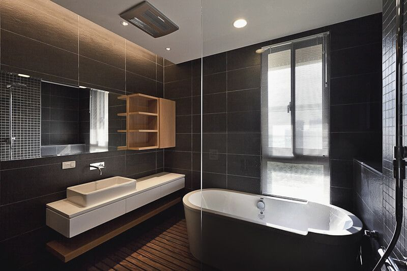 This luxurious bathroom has sleek dark tile walls and beautiful dark hardwood flooring. Hints of white in the bathtub and the countertop create a breath taking contrast against the dark walls.