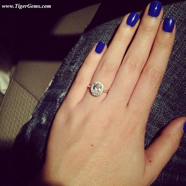"""""""I'm SOOO in love with this ring! It's absolutely perfect. Thank you so much!"""" 💙💎✨ #Thankyou to my wonderful client for this gorgeous photo! She is wearing the 1 carat oval cut halo ring. It's on sale now at www.TigerGems.com. 🐯✨ #lovemyclients #handmade #sparkle #custom #oval #haloring #diamondring #manmadediamond #proposal #love #engagementring #birthdaygirl #promisering #anniversary #nails #blue #datenight  #dreamring #bling #bridal #wedding #bridesmaid"""