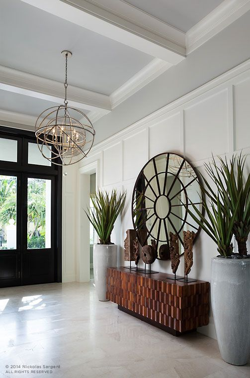 Entryway with black front door large round mirror orb chandelier moulding on ceiling