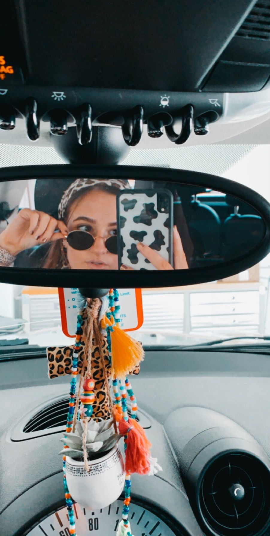Photo of Car mirror selfie, cheetah headband, Rayban sunglasses, wildflower cow print cas…