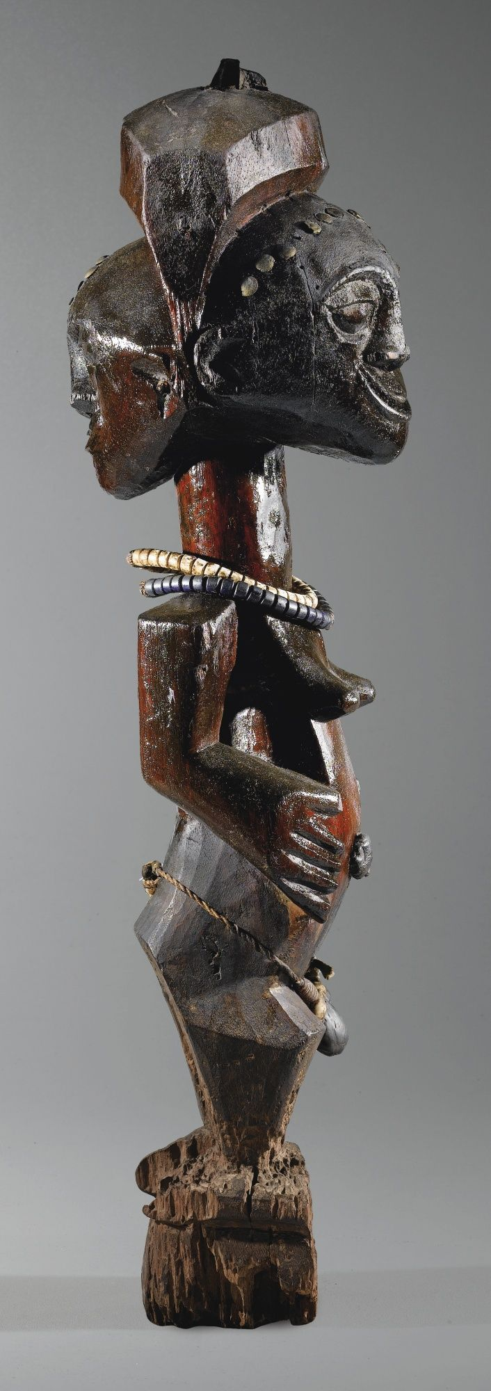 Africa   Janus form figure from the Songye people of DR Congo   Carved from reddish wood with a frontal diadem made up in brass studs, a braided rope adorned with glass beads and a ritual agglomerate contained in a small seed bag serves as a belt.   2nd half of the 19th century
