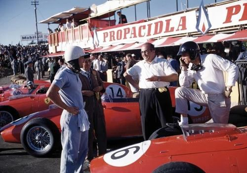 American drivers Phil Hill (white helmet) & Dan Gurney (black helmet) talking to Ferrari designer Carlo Chiti & team boss Enzo Ferrari next to their Ferrari Dino 246's during the 1959 Portuguese Grand Prix at the Circuito do Monsanto in Lisbon.