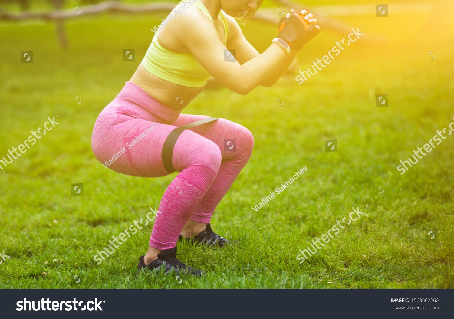 Sporty woman doing squats with fitness gum expander in the park outdoors ,