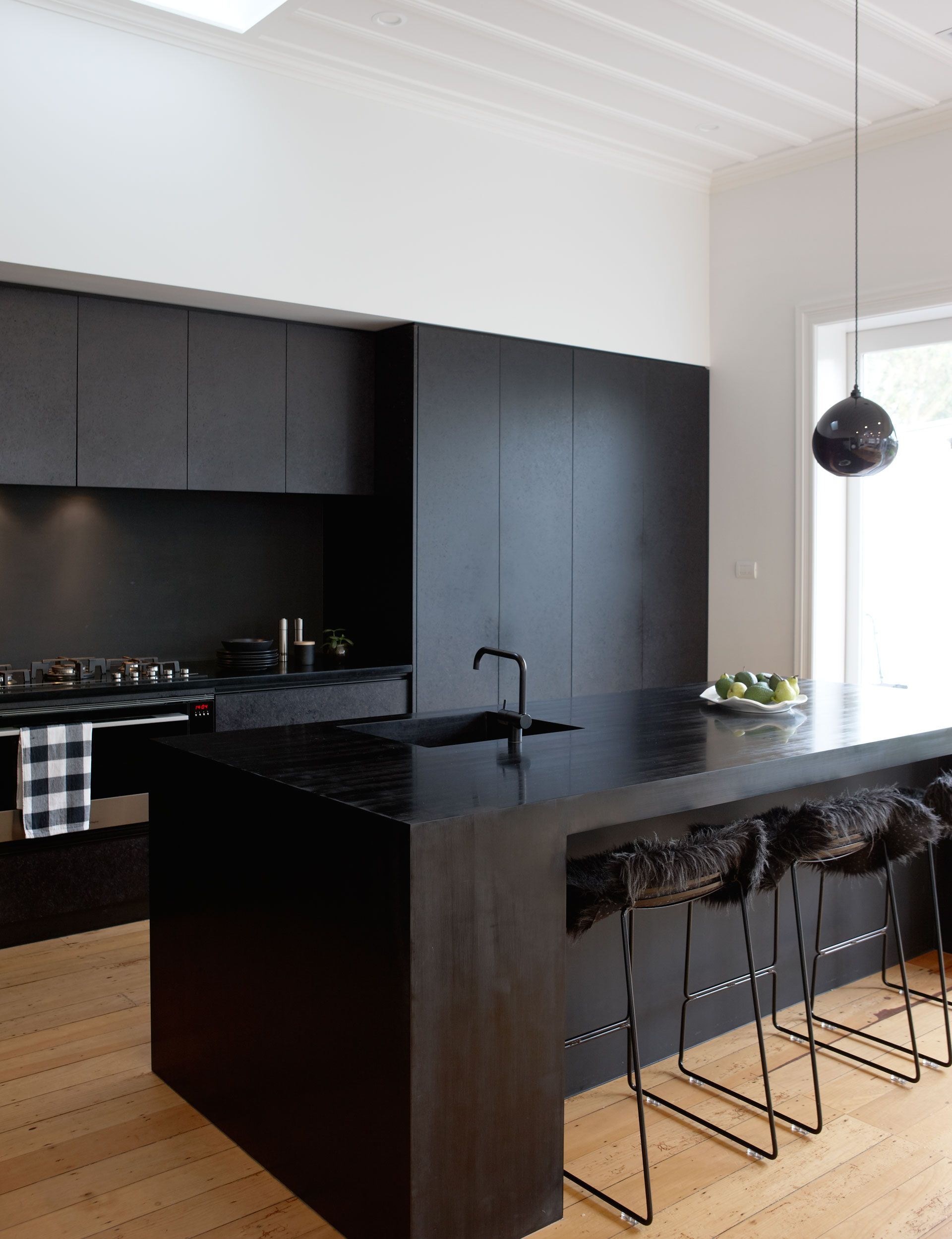 A matte black kitchen makes a bold statement in this Auckland villa