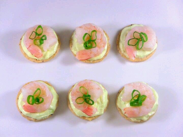Mix wasabi and sour cream,  put over rice cracker with cooked shrimp top with chives for a great appetizer for the holidays!