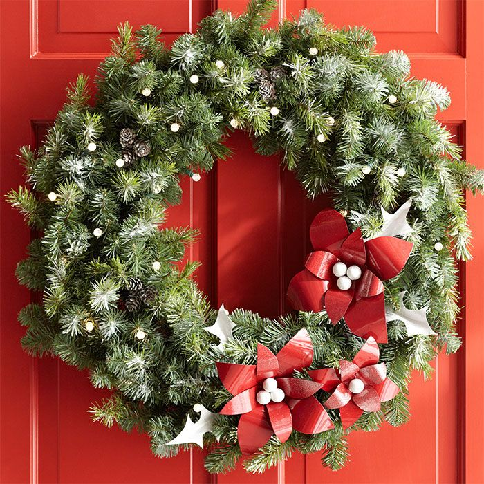 Lighted Christmas wreath with large red flower shapes and hung on ...