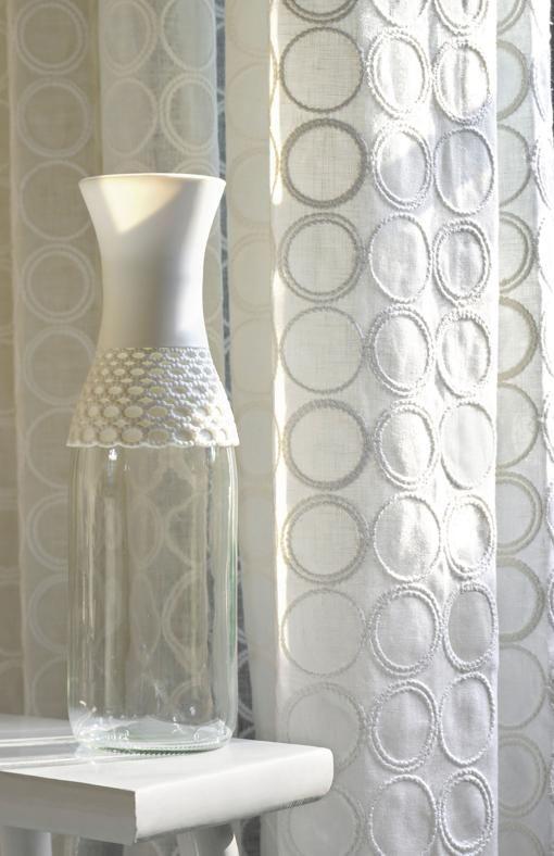 Decorare con i tessuti ELITIS Tenda in morbido lino bianco della serie Dolcezza impreziositi da cerchi ricamati di ispirazione neo-Seventies.